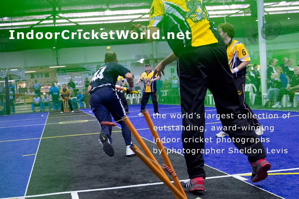 close up of indoor cricket wicket-keeper throwing to bowler's end to run out batsman, stumps scattered, batsman scrambling to other end, ball in flight